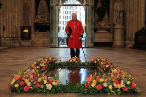 A Chelsea Pensioner by the Grave of the Unknown Warrior with Fresh flowers signifying the end of the 1WW.